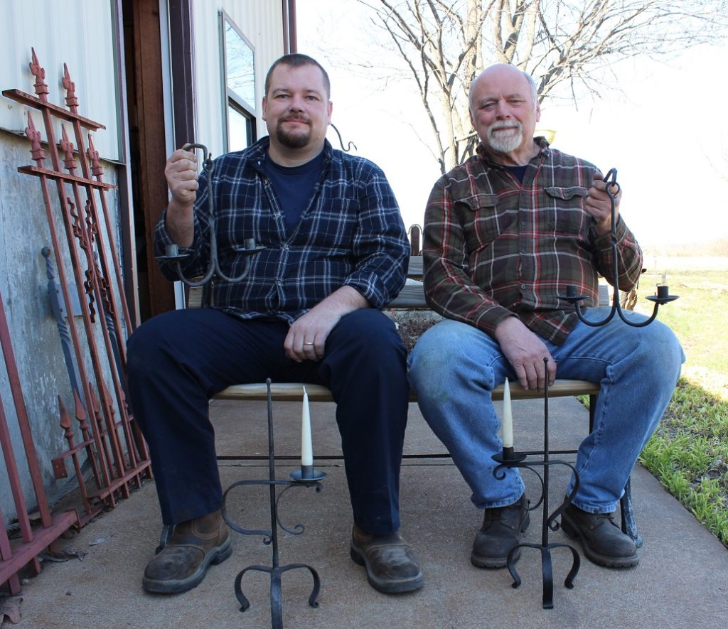 Photo of apprentice Matt Dickson and master blacksmith Bob Alexander sitting outside Scrub Oak Forge holding lamps.